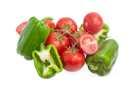 Branch with the ripe red tomatoes, several green bell peppers and bisected one tomato and bisected one pepper on a light background
