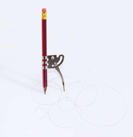 Simple school metal compass and the inserted into it common pencil with attached eraser drawing the circles of different diameters on a white sheet of a paper Stock Photo
