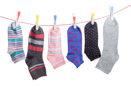 Several different varicolored men's and women's socks hanging on the clothes line with plastic clothespins on a light background