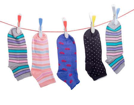Several different varicolored womens socks hanging on the clothes line with plastic clothespins on a light background Stock Photo