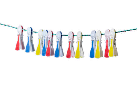 Several spring-type plastic clothespins with varicolored rubber inserts hanging on the clothes line on a light background