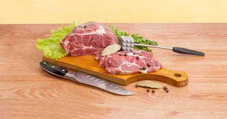 Partly sliced uncooked pork neck, lettuce leaves and spices on wooden cutting board, bunch of the parsley,  meat tenderizer and kitchen knife on a wooden surface Stock Photo