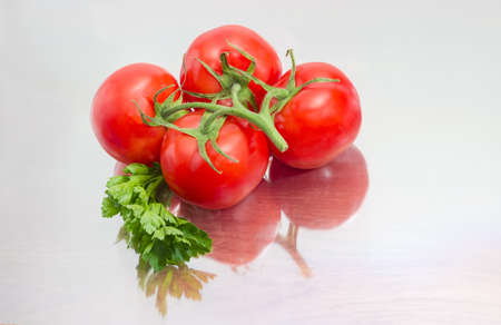 Branch of the ripe red tomatoes and twig of the parsley closeup on a matt reflective surface Imagens