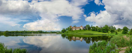 Panorama of pond after a thunderstorm with ancient castle on the opposite bank. Svirzh Castle built in the 15th century, Lviv region, Ukraine.