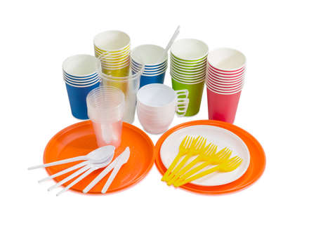 Orange and white disposable plastic plate, spoons, forks and knives, disposable paper cups in different colors, different white and transparent disposable plastic cups on a light background