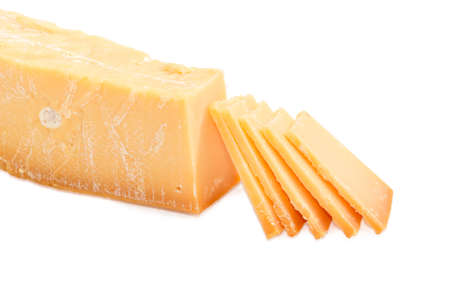 Several thin slices of the Dutch hard cheese Beemster on a dark glass saucer and piece of the same cheese beside on a light background  Stock Photo