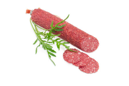 potherb: Partly sliced salami and fresh twig of the arugula on a light background Stock Photo