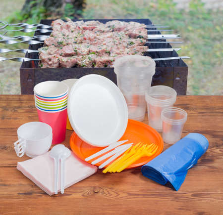 Different disposable plastic and paper cutlery, paper napkins and roll of disposable garbage bags on the old wooden planks against the background of barbecue grill with grilled skewered meat outdoors Stock Photo - 80049298