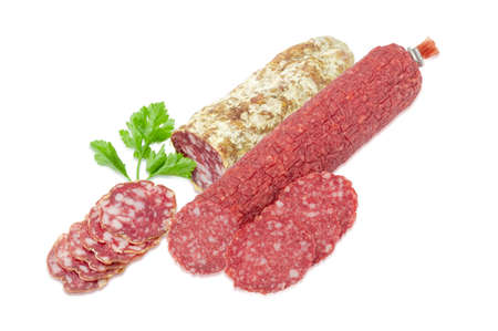 dry sausage: Partly sliced two kinds of the salami with fresh twig of parsley on a light background