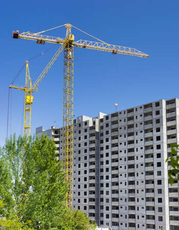 latticed: Two different tower cranes with latticed booms on a construction of a multi-story residential building and trees in the foreground
