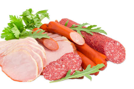 charcutería: Sliced boiled smoked pork loin and ham, partly sliced salami and hunting sausages with arugula and parsley closeup on a light background Foto de archivo