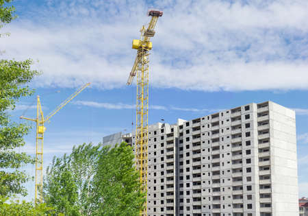 latticed: Two different tower cranes with latticed booms on the background of the upper part of a multi-story residential building under construction, tree and sky