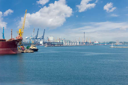 Part of the sea cargo port with several berth with different harbor cranes and bow of the ship in the foreground Stock Photo