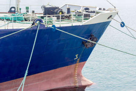 Bow of the old cargo ship with a blue starboard moored by several mooring ropes to the berth of the sea cargo port closeup