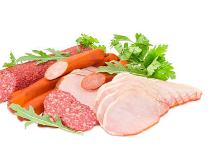 Sliced boiled smoked pork loin and ham, partly sliced salami and hunting sausages with arugula and parsley closeup on a light background Stock Photo