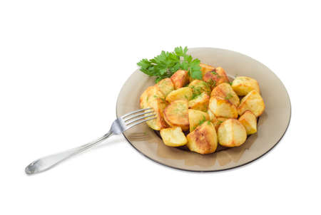 Serving of the country style fried potatoes sprinkled by chopped dill and twig of parsley on dark glass dish and fork on a light background Stock Photo