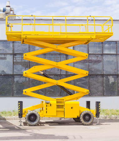 Gele schaar op wielen lift op een asfaltgrond op de achtergrond van het industriële gebouw