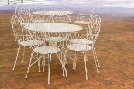 Witte metalen tafels en stoelen met opengewerkte ruggen op de vloer gemaakt van bruine tegels in een zomercafé