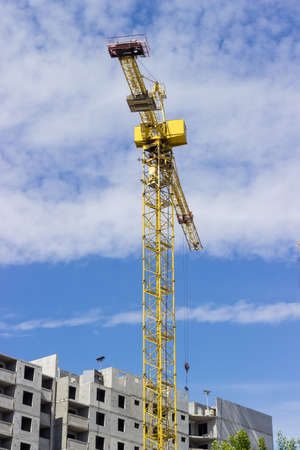 Tower crane with latticed boom on the background of the upper part of a multi-story residential building under construction and sky Stock Photo