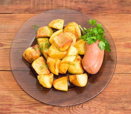 potherb: Top view of the dark glass dish with fried potatoes sprinkled by chopped dill, fried wieners and twig of parsley closeup on a surface of old wooden planks