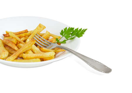 elongated: Fragment of the white dish with the French fries and twig of parsley and fork of stainless steel on a light background