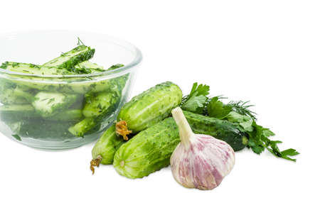 Fragment of the glass bowl with lightly salted cucumbers and several freshly picked out cucumbers, parsley, dill and garlic