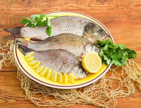 Carp and crucians different sizes with peeled scales and prepared for cooking, slices of lemon and parsley twigs on the yellow dish and part of the fishing net on a surface of the old wooden planks