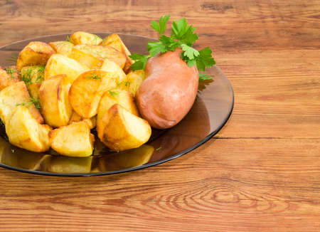 Fragment of the dark glass dish with fried potatoes sprinkled by chopped dill, fried wieners and twig of parsley closeup on a surface of old wooden planks Stock Photo
