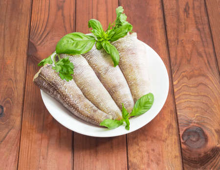 Uncooked carcasses of the notothenia fish without of a heads and tails and with peeled scales and prepared for cooking, twigs of basil and parsley on the white dish on a dark wooden surface Stock Photo