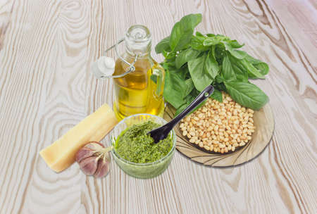 Sauce basil pesto in the small glass bowl with small black ceramic spoon on a background of ingredients for its preparation on a wooden surface Stock Photo