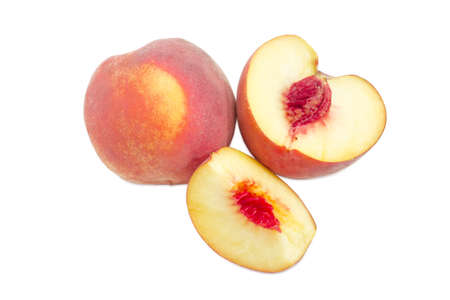 One whole and one cut into slices ripe fresh peaches on a white background Stock Photo