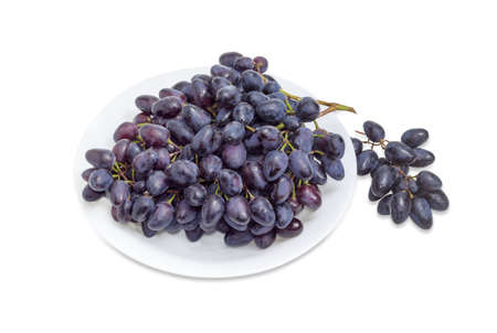 Big cluster of the ripe dark blue table grapes on a white dish and small grape cluster beside on a white background