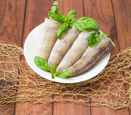 Carcasses of the notothenia fish without of a heads and tails and with peeled scales and prepared for cooking, basil and parsley twigs on the white dish on a dark wooden surface with fishing net