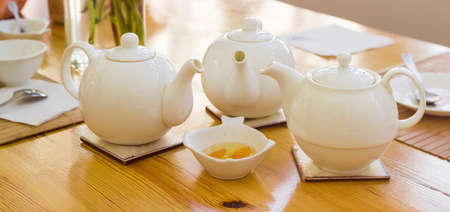 trivet: Panorama of the three white teapot on a ceramic trivets on a wooden table on a background of a tea appliances Stock Photo