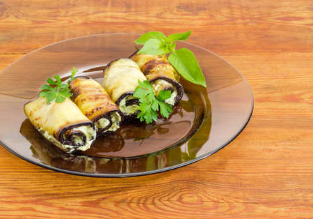 Fragment of a dark glass dish with several eggplant rolls stuffed with tuna and processed cheese and decorated with parsley and basil twigs on a surface of an old wooden planks Stock Photo