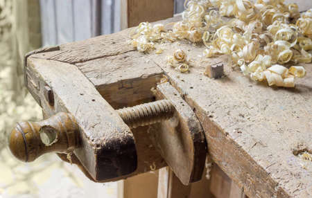 vise: Fragment of old woodworking workbench with two fixing device of workpieces - planing stop and shoulder vise with wooden screw and shavings on workbench