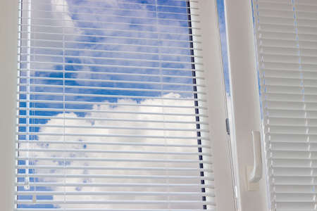 Fragment of the modern plastic window with Venetian blinds and view of the sky with clouds across slats of a window blind