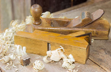 Two old wooden hand planes different purposes among a shavings on the old woodworking workbench with planing stop on foreground