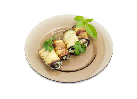 Eggplant rolls with tuna and processed cheese filling decorated with parsley and basil twigs on a dark glass dish on a white background Stock Photo