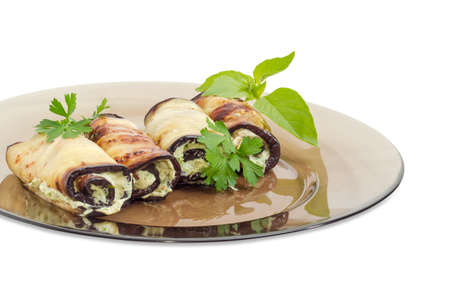 Fragment of a dark glass dish with several eggplant rolls stuffed with tuna and processed cheese and decorated with parsley and basil twigs on a white background  closeup