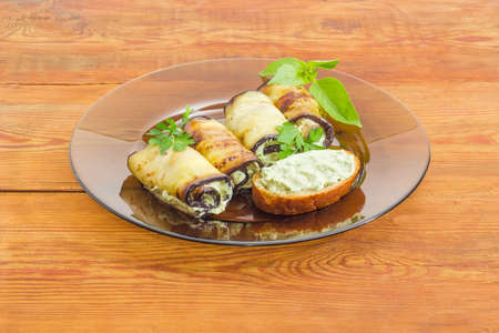 Eggplant rolls with tuna and processed cheese filling decorated with parsley and basil twigs and sandwich with stuffing on a dark glass dish on a surface of an old wooden planks