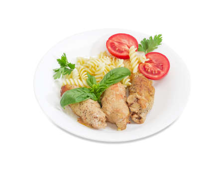 Braised meat roulades with filling from bread dried crusts and mushrooms and beside spiral pasta and tomato, decorated with basil and parsley twigs on a white dish on a white background