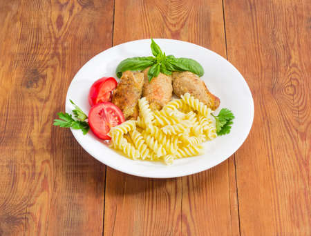 Braised meat roulades with filling from bread dried crusts and mushrooms, tomato and spiral pasta decorated with basil and parsley twigs on a white dish on a surface of an old wooden planks