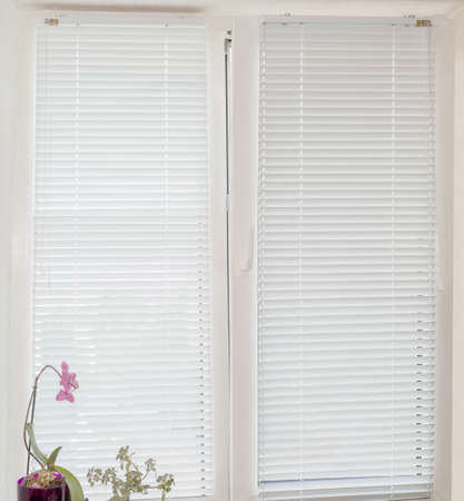 White Venetian blinds with manual control on the modern tilt and turn plastic window