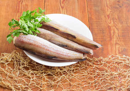 alaska pollock: Uncooked carcasses of the Alaska pollock without of head and tail and bundle of parsley on a white dish on a surface of old wooden planks with fishing net Stock Photo