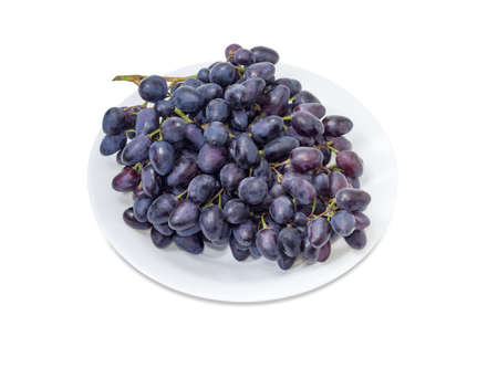 aon: Big cluster of the ripe dark blue table grapes on a white dish aon a white background Stock Photo