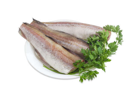 alaska pollock: Three uncooked carcasses of the Alaska pollock without of head and tail and bundle of parsley on a white dish on a white background Stock Photo
