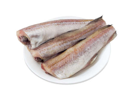 alaska pollock: Three uncooked carcasses of the Alaska pollock without of head and tail on a white dish on a white background