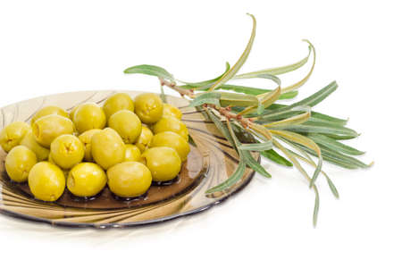 Fragment of a dark glass saucer with canned green olives and olive branch beside on a white background