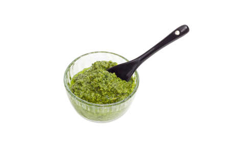 Sauce basil pesto in the small glass bowl with black ceramic small spoon on a white background